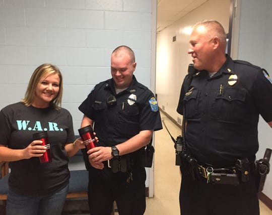 We Are Recovery member Sara Blake presents Zaneville police officers with stainless steel travel mugs in appreciation for saving the lives of overdose victims.