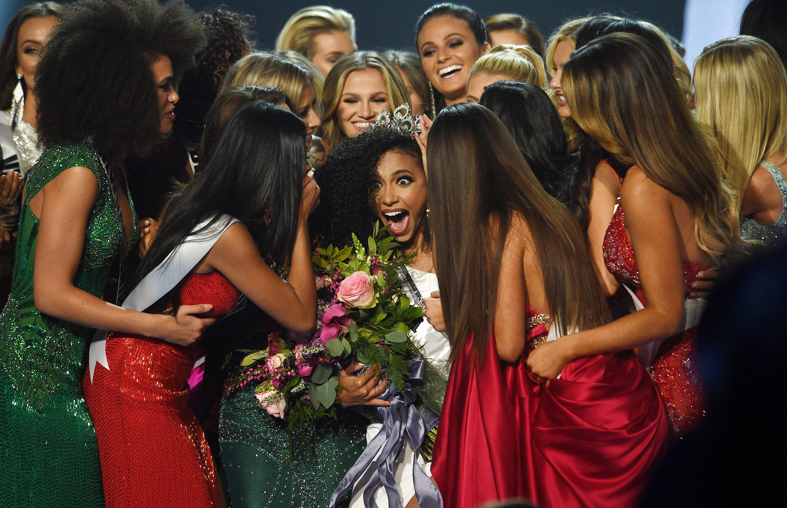 Miss North Carolina Chelsie Kryst, middle, is mobbed by fellow contestants after winning Miss USA 2019.