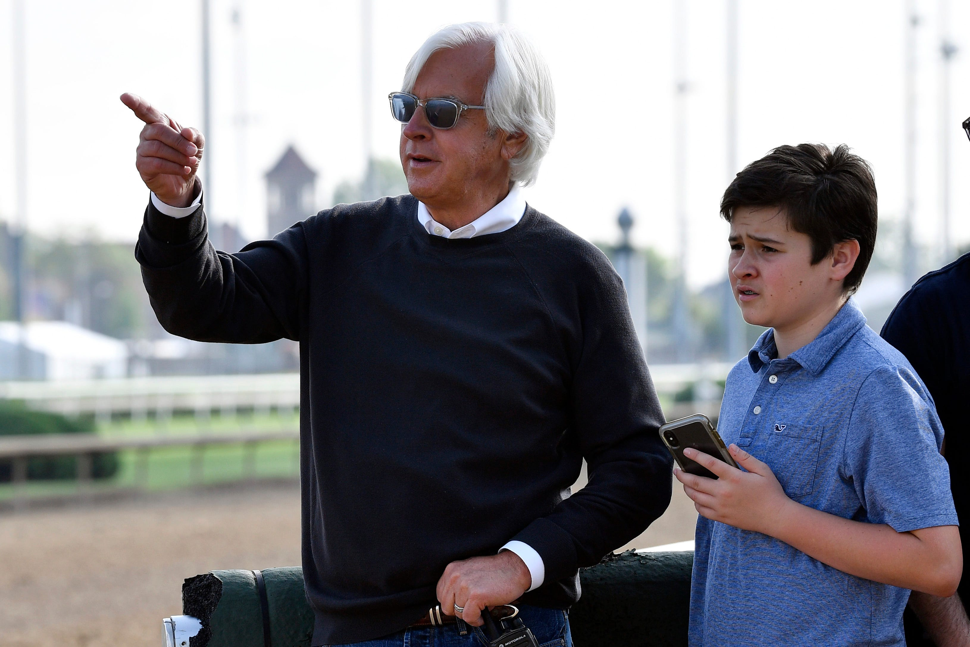 Trainer Bob Baffert and his son Bode watch Kentucky Derby entry Game Winner during morning workouts at Churchill Downs.
