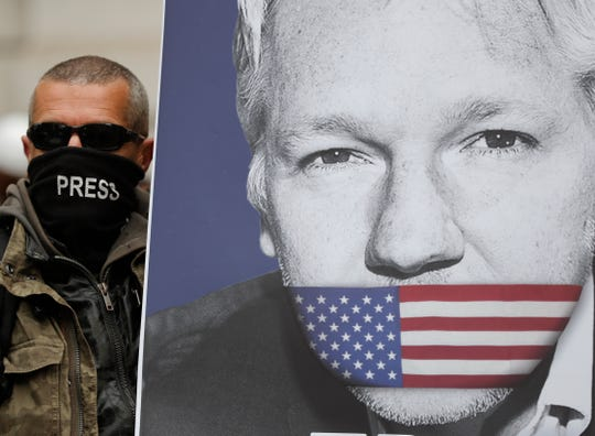 A supporter of Julian Assange with a poster of the WikiLeaks founder joins other protesters to block a major road in front of Westminster Magistrates Court in London on May 2, 2019.