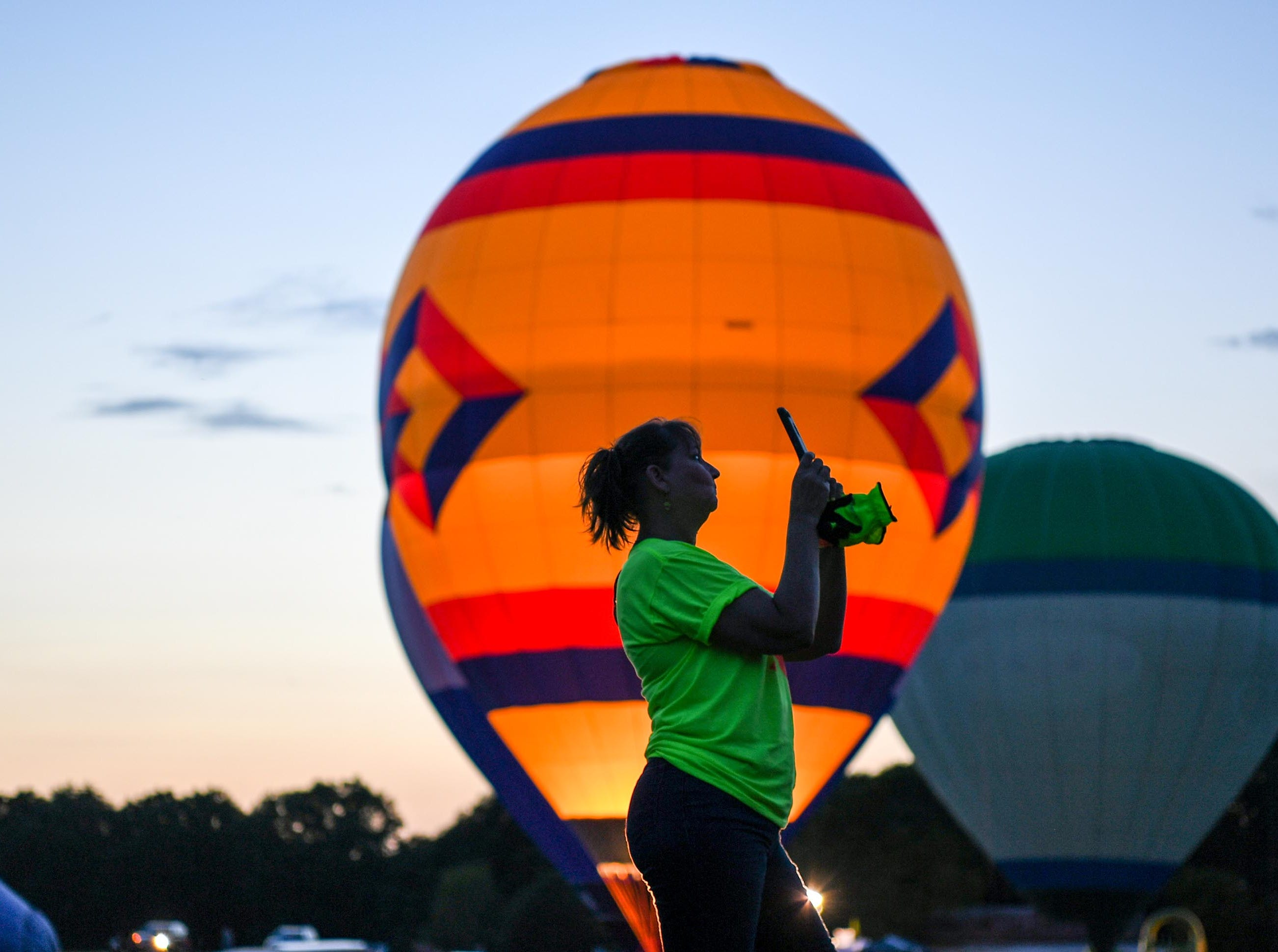 A woman takes a photo at the balloon glow at the Rocky River Plantation during the Cancer Association of Anderson Hot Air Balloon Affair in Anderson Friday.