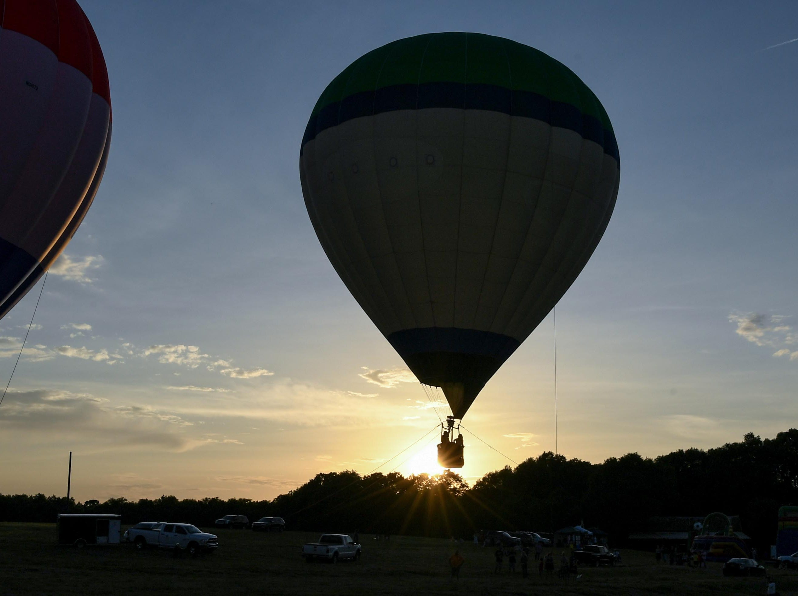 Balloons rise before an evening glow at the Rocky River Plantation during the Cancer Association of Anderson Hot Air Balloon Affair in Anderson Friday.