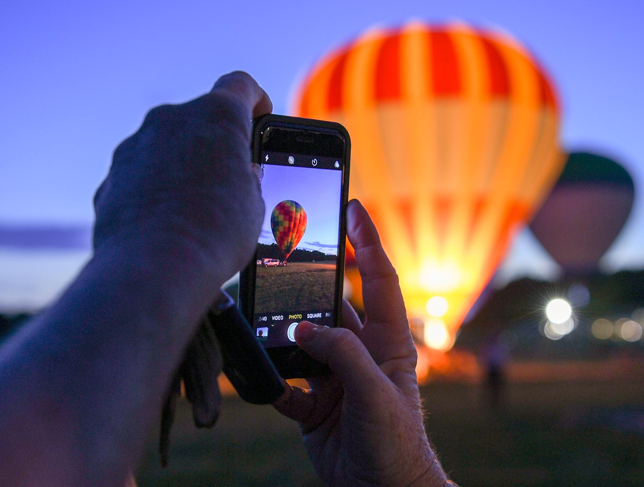 A visitor takes a photo of the balloon glow at the Rocky River Plantation during the Cancer Association of Anderson Hot Air Balloon Affair in Anderson Friday.