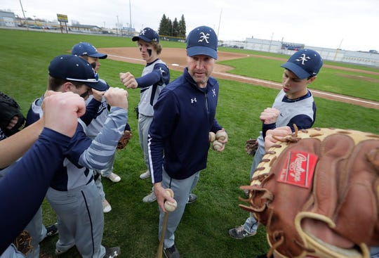 Xavier head coach Tim Harikkala talks to his team before Thursday's game against Menasha at Don Hawkins Field.