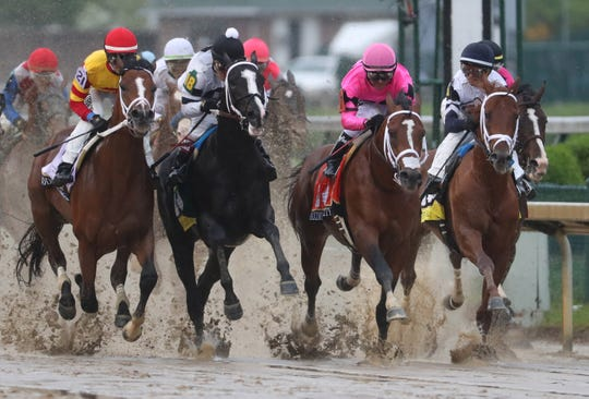 MLuis Saez aboard Maximum Security (7) , Chris Landeros aboard Bodexpress (21) and Jon Court aboard Long Range Toddy (18) race during the 145th running of the Kentucky Derby at Churchill Downs.