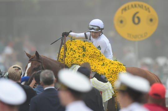 Mike Smith places Black-Eyed Susan bed of flowers on top of Justify (7) after winning the 143rd running Preakness Stakes at Pimlico Race Course.