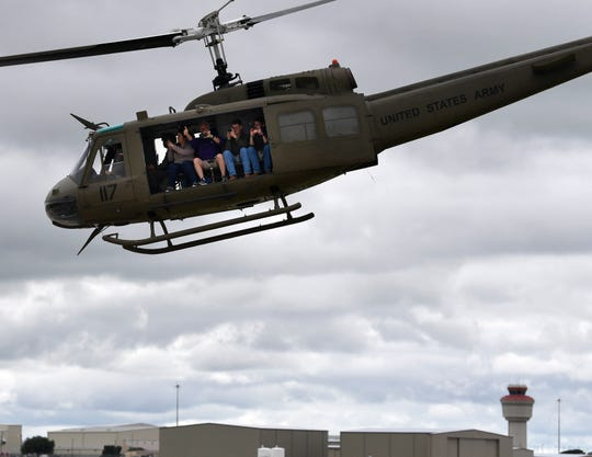 """Passengers record video as they fly over Abilene Regional Airport in a UH-1 """"Huey"""" helicopter."""