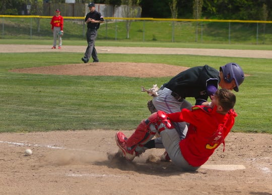 North Kitsap's Isaac Richardson collides with Franklin Pierce catcher Connor Delano during Saturday's Class 2A West Central District tournament baseball game at the Kitsap County Fairgrounds. Richardson was ruled out on the play for running into the catcher.