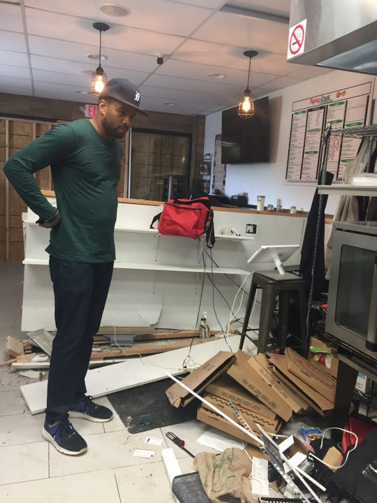 Flying Crust pizza and wings shop owner Garis Eddington surveys some of the damage after a car crashed into the store front Friday night, May 3, 2019