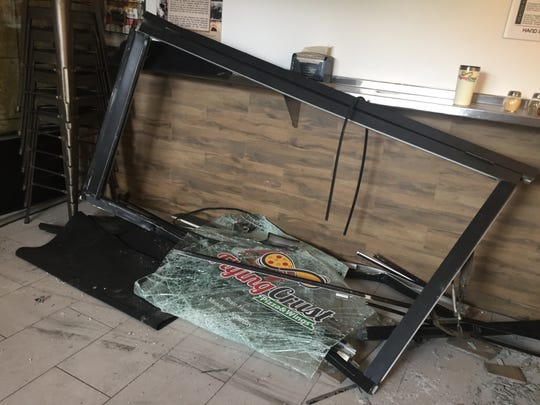 Damaged glass front door lays inside Flying Crust pizza and wings shop after it was hit by a car that drove into the shop May 3, 2019,  injuring store workers