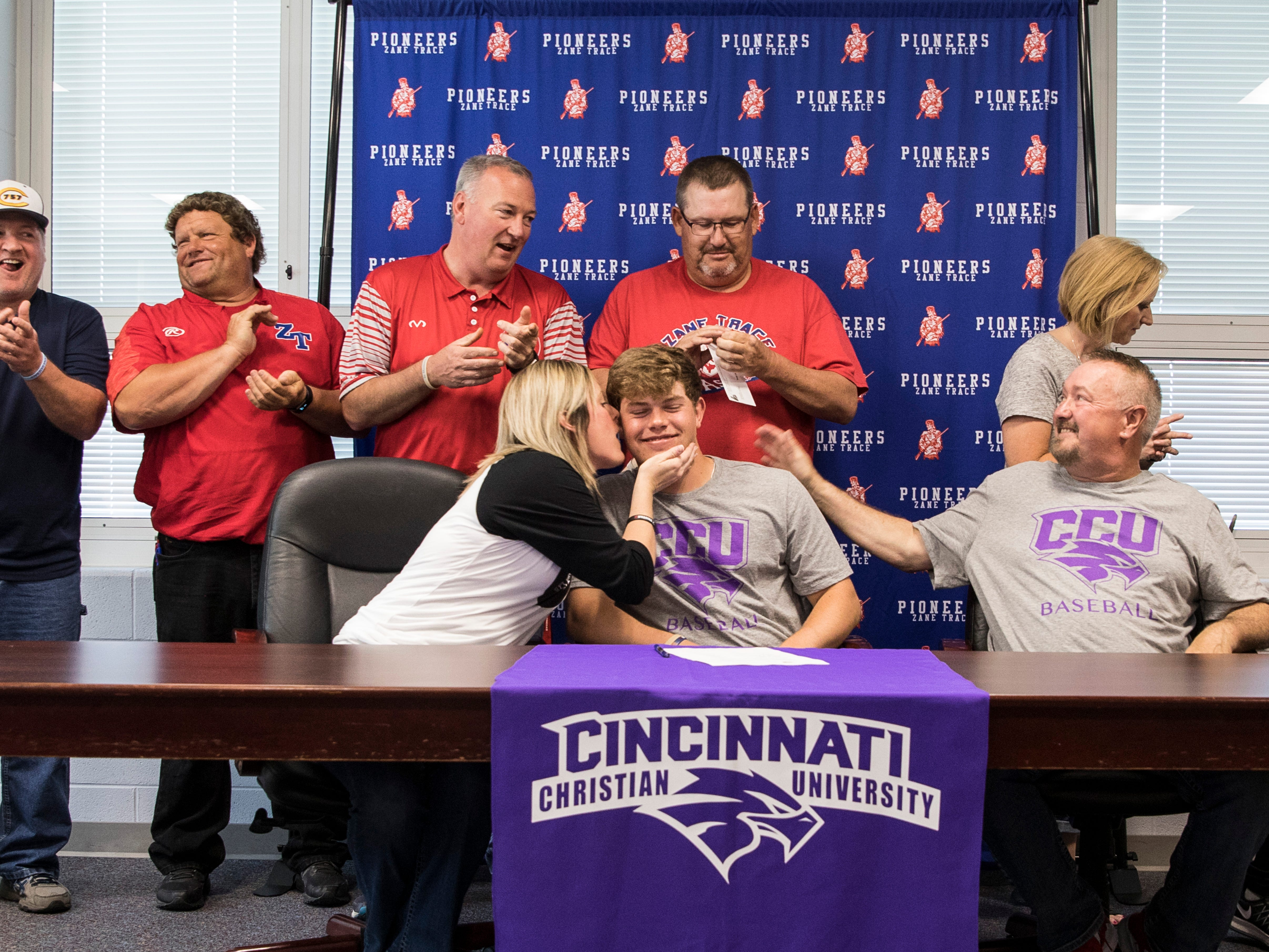 Zane Trace senior Chad Ison gets a kiss from his mother Sharie Betts McNeely after officially signing to play baseball for Cincinnati Christian University on May 2, 2019 at Zane Trace High School.