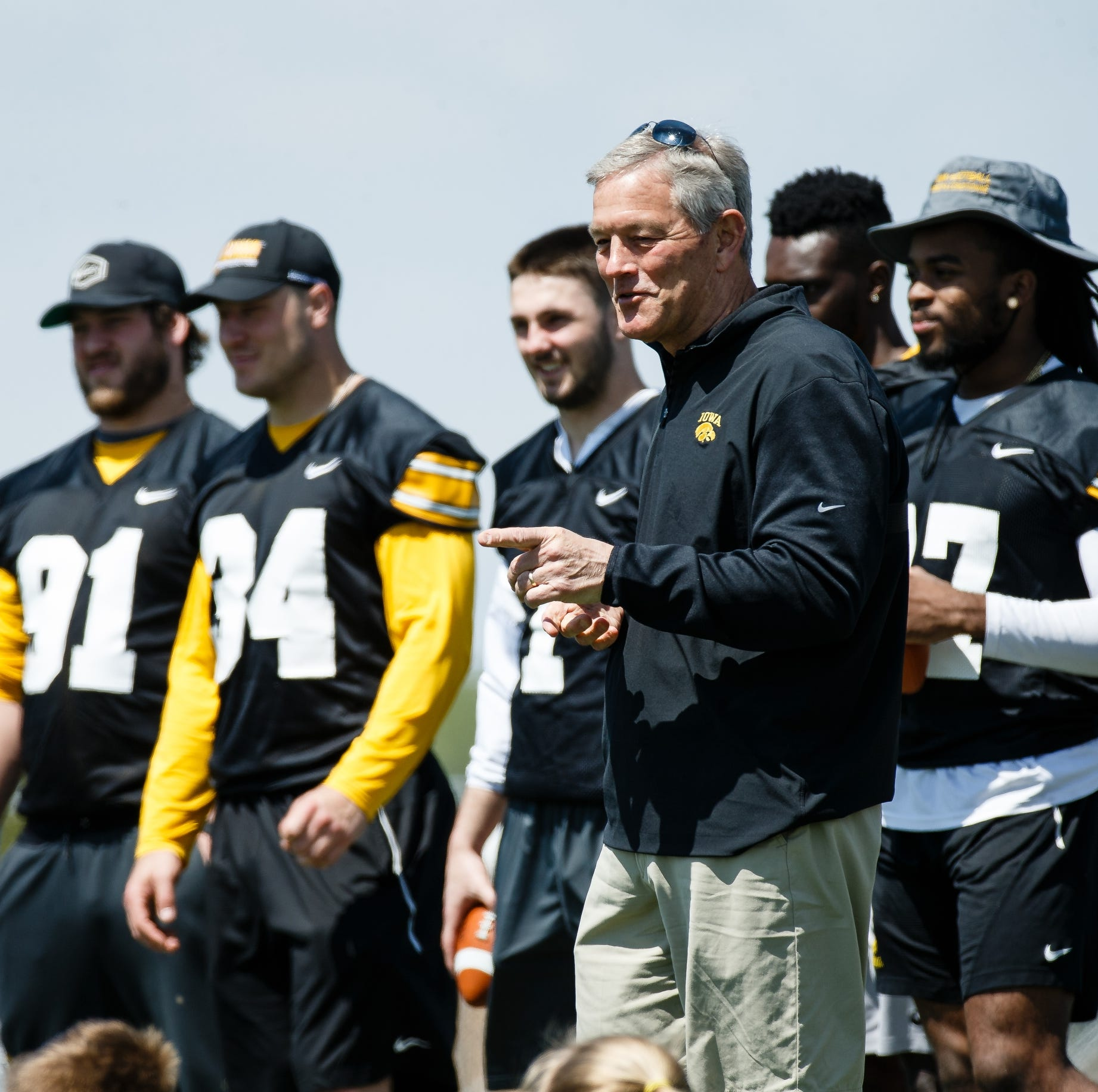 Coach Kirk Ferentz talks to campers after...
