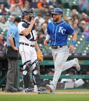 John Hicks watches as Royals left fielder Alex Gordon scores Saturday.
