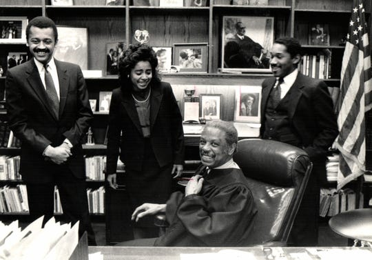 Judge Damon Keith sits in the chair of his office with law clerks Claude Bailey, left, Renee Chenault and Gerry Hargrove. Keith, a federal judge, was known for his ability to engage others such as law clerks, community leaders and journalists, in the fight for civil rights.