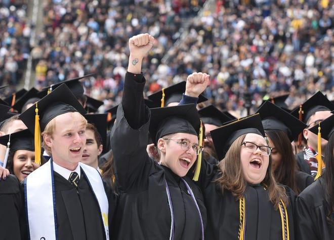 "University of Michigan graduate Audra Christophersen (center) shouts, ""Go blue."""