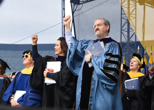 Gov. Gretchen Whitmer and University of Michigan President Mark Schlissel cheer to the UM fight song at the end of commencement on Saturday, May 4, 2019.
