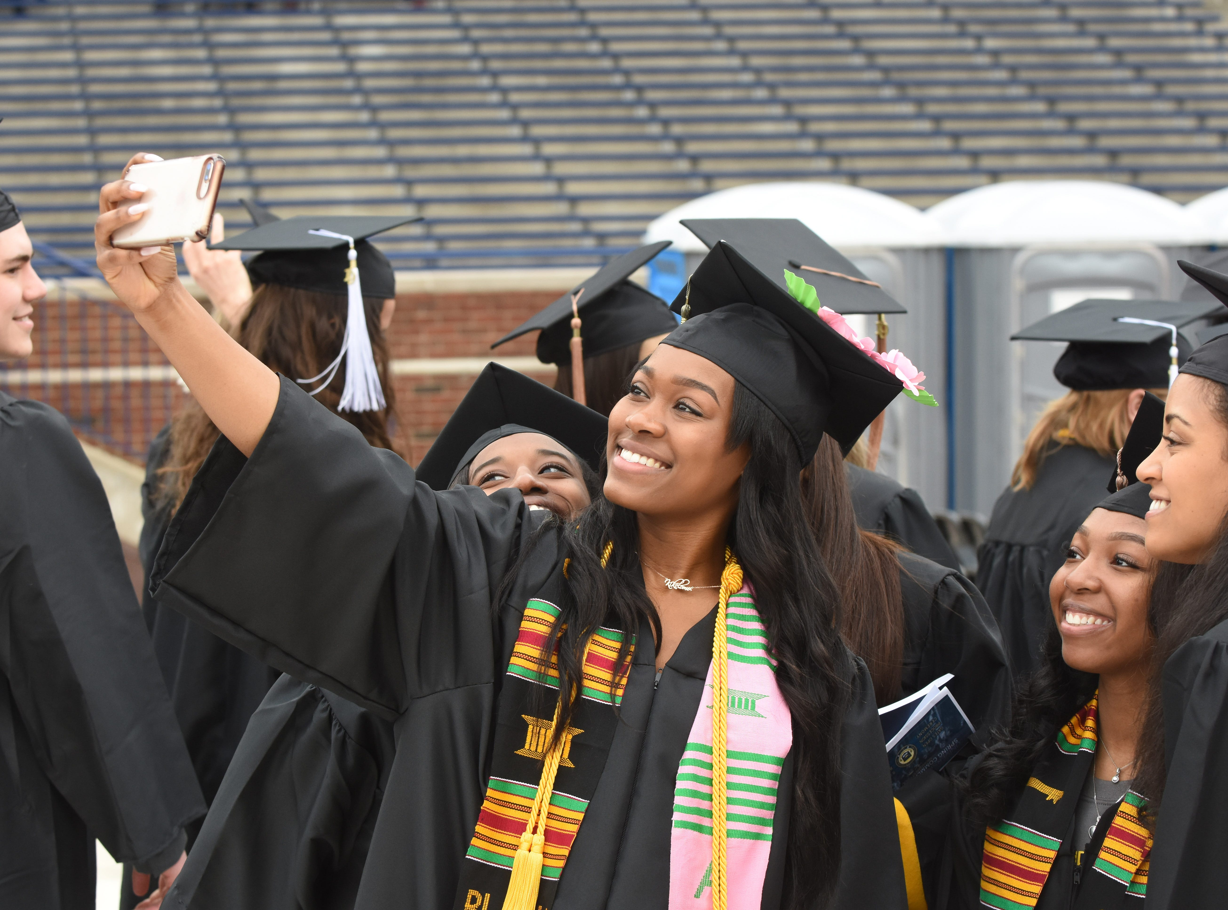 University of Michigan student Kikel Sekoni  takes a selfie with fellow graduates.