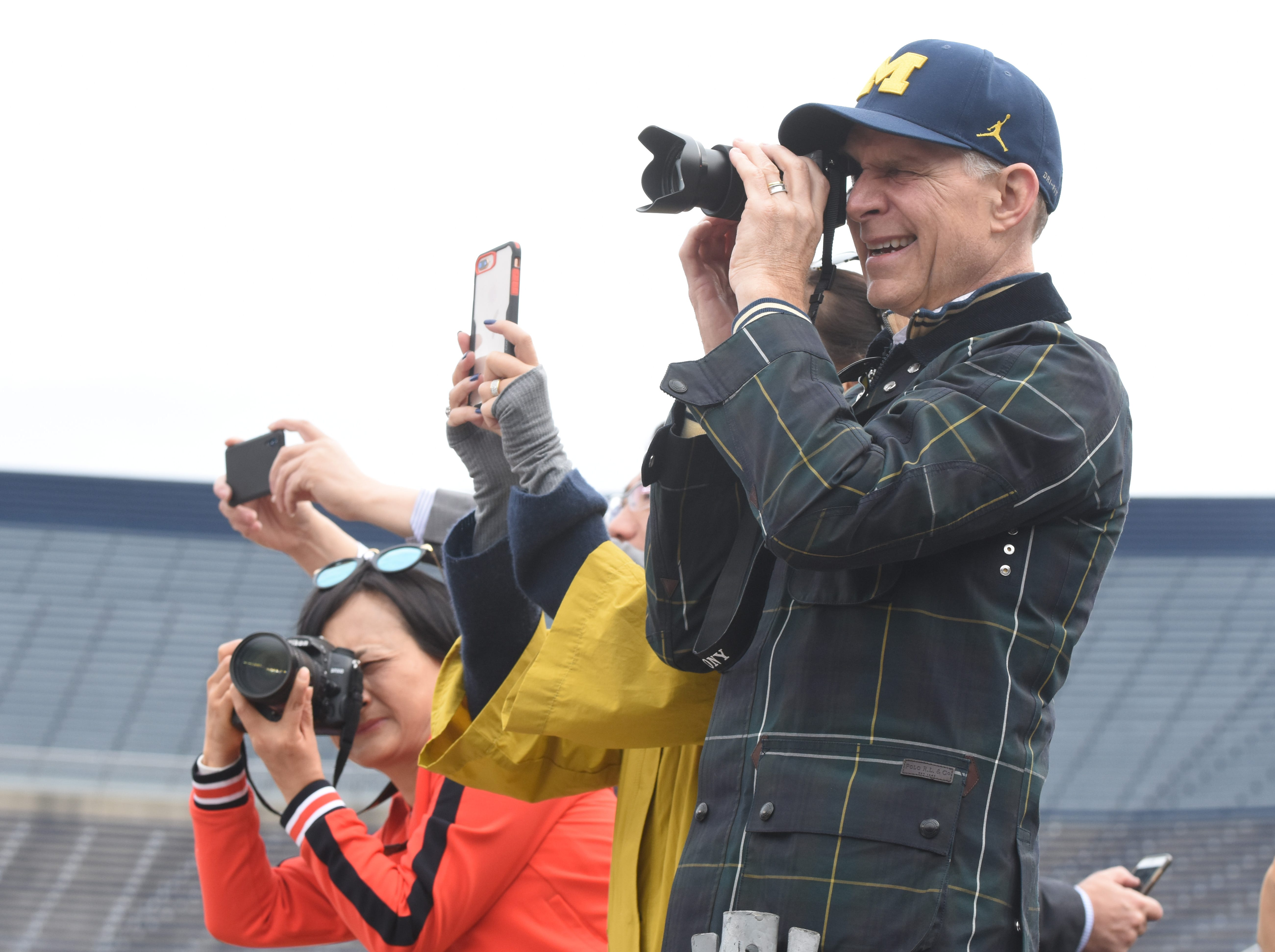 Family and friends of University of Michigan students take photographs during commencement exercises.