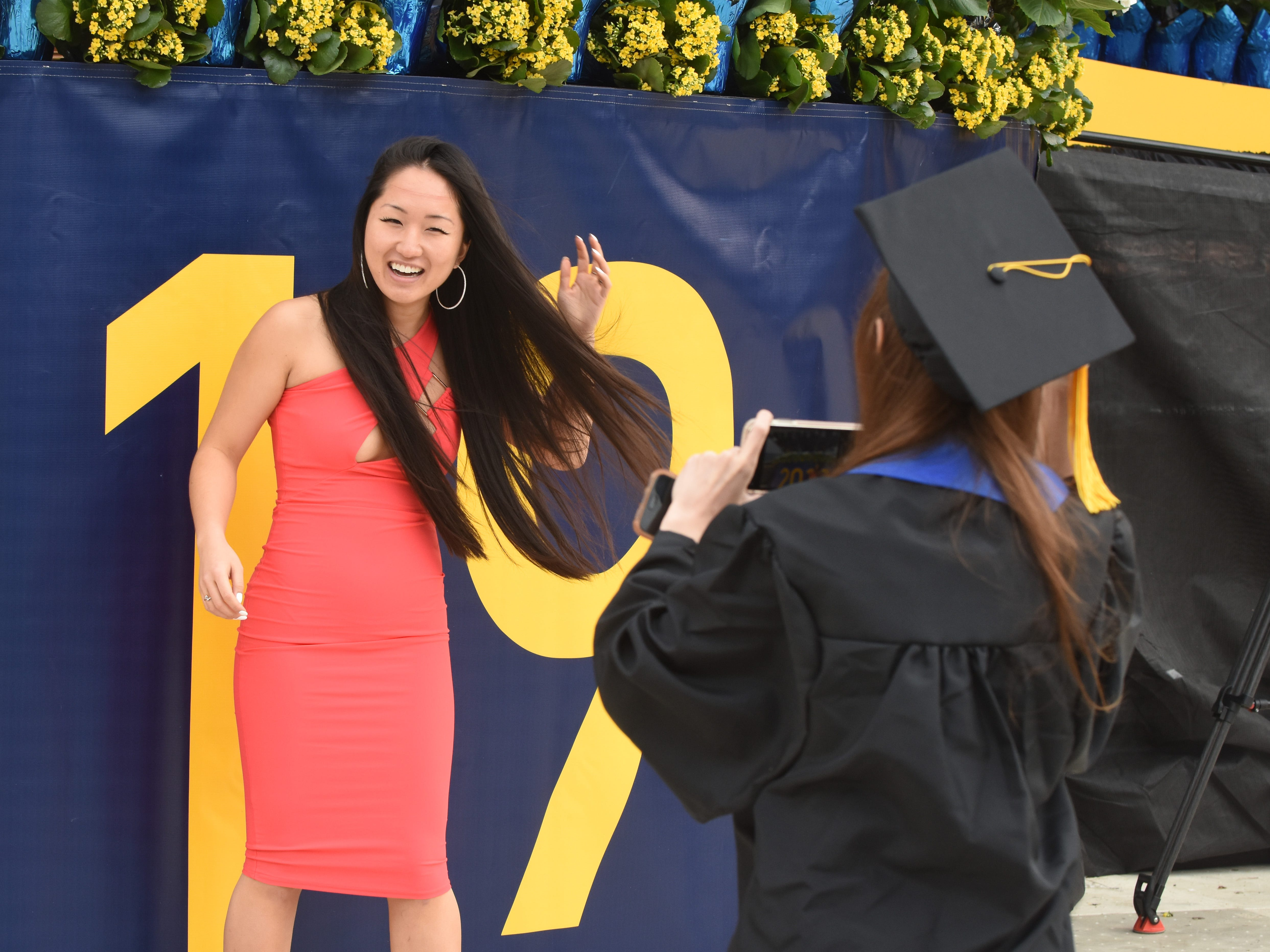 University of Michigan student Martina Cholagh (right) takes a picture of Tatiana Yugay in a bright pink dress she was wearing under her graduation gown during commencement exercises in Ann Arbor.