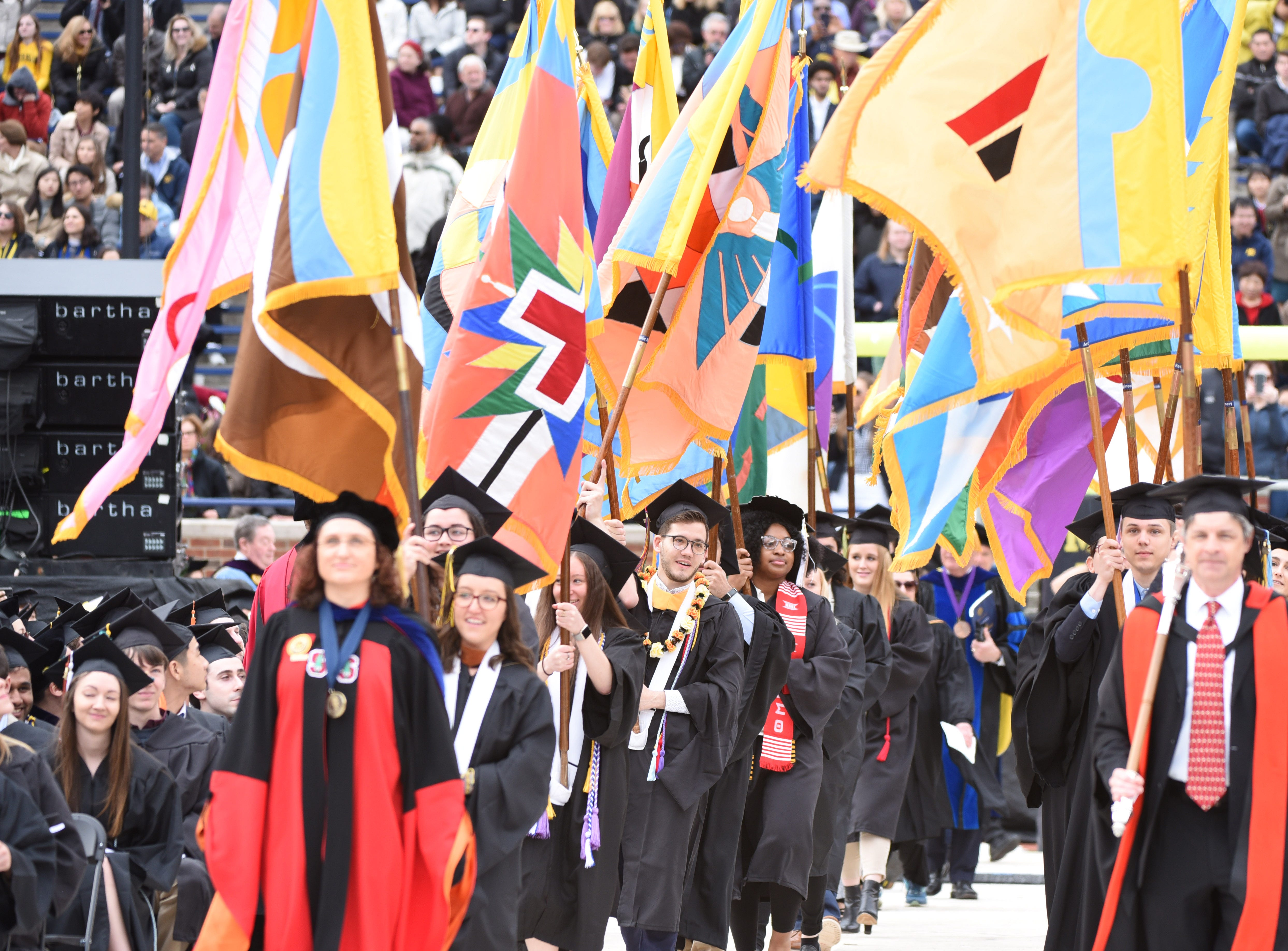 University of Michigan faculty are surrounded in colorful flags as they enter the Big House for commencement  in Ann Arbor.