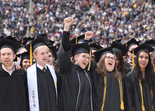 """The University of Michigan's Audra Christophersen, center, shouts """"go blue"""" during commencement exercises in Ann Arbor on Saturday, May 4, 2019."""