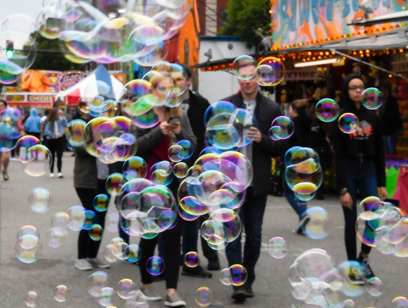 Tiny bubbles from a carnival hawker fill the air at the 32nd annual Breakfast Lions Club Tri-Fest in downtown Henderson Saturday, April 27, 2019.