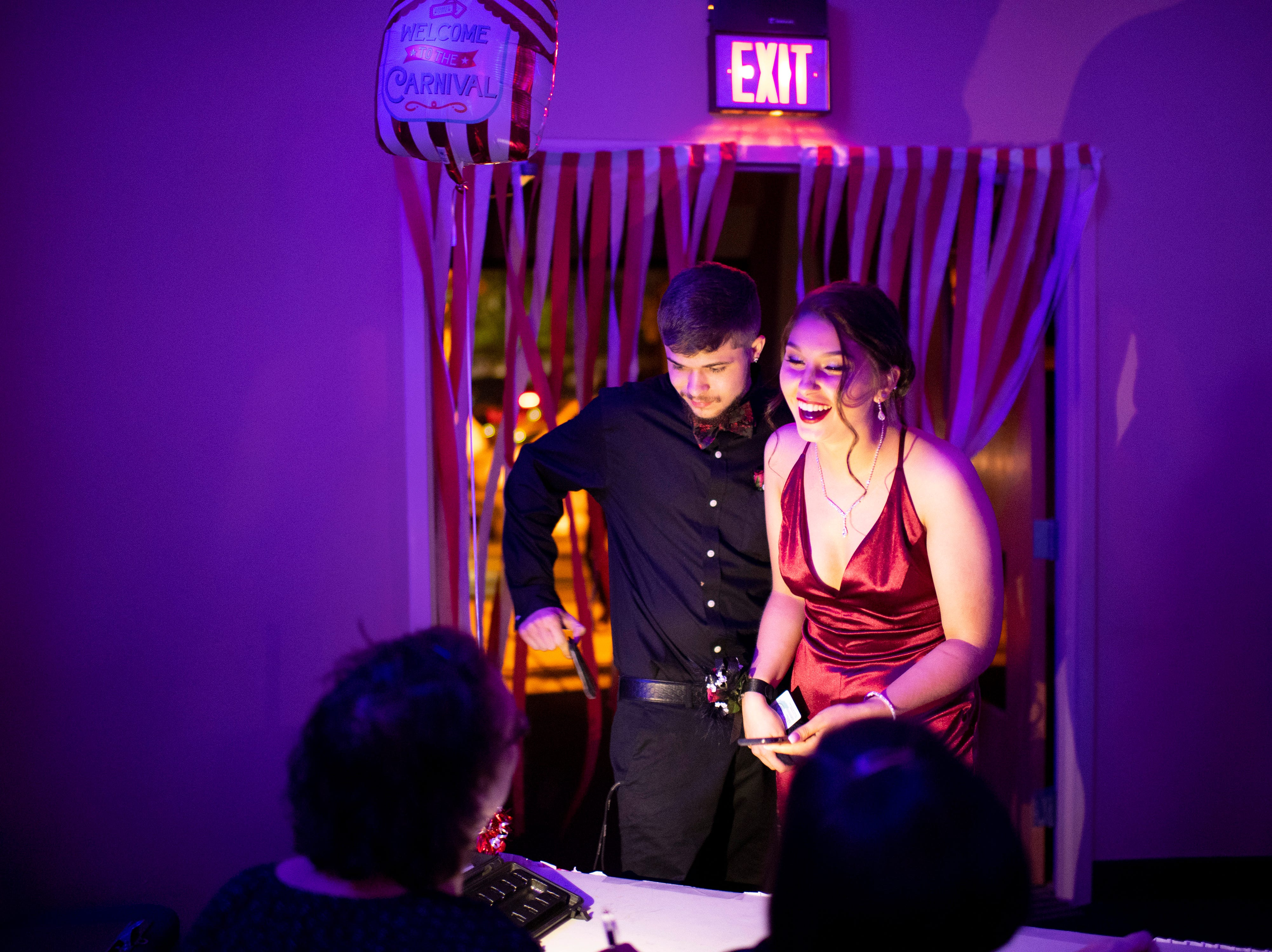 """Harrison seniors Cassidy Shafer and Sebastian White check in to """"The Greatest Prom on Earth"""" at Milestones, Saturday night, April 13, 2019."""