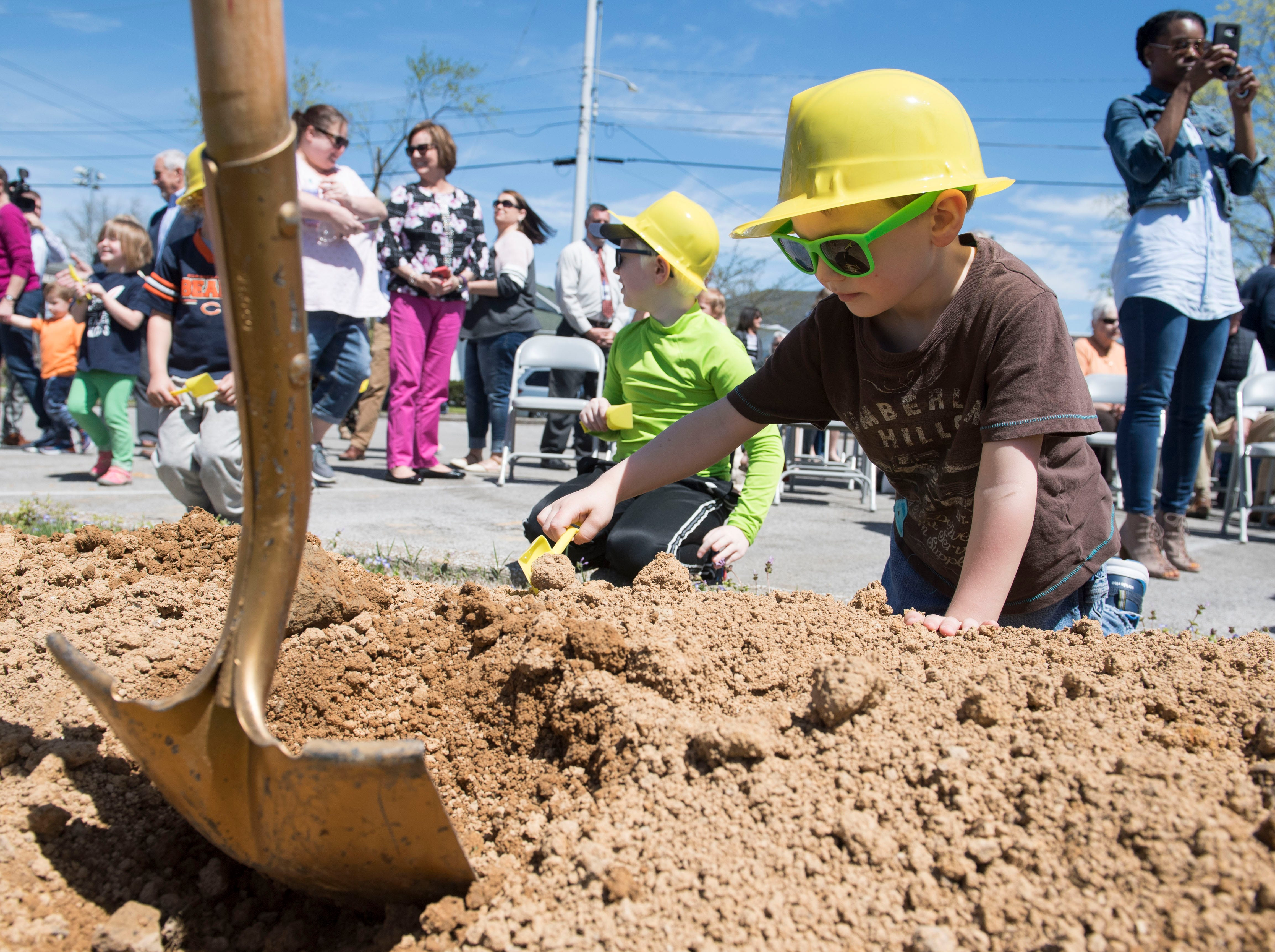 James May, Henderson County Public Library Director's son, plays in the dirt after a ground breaking of the libraries $8 million addition and renovation, Tuesday, April 9, 2019.