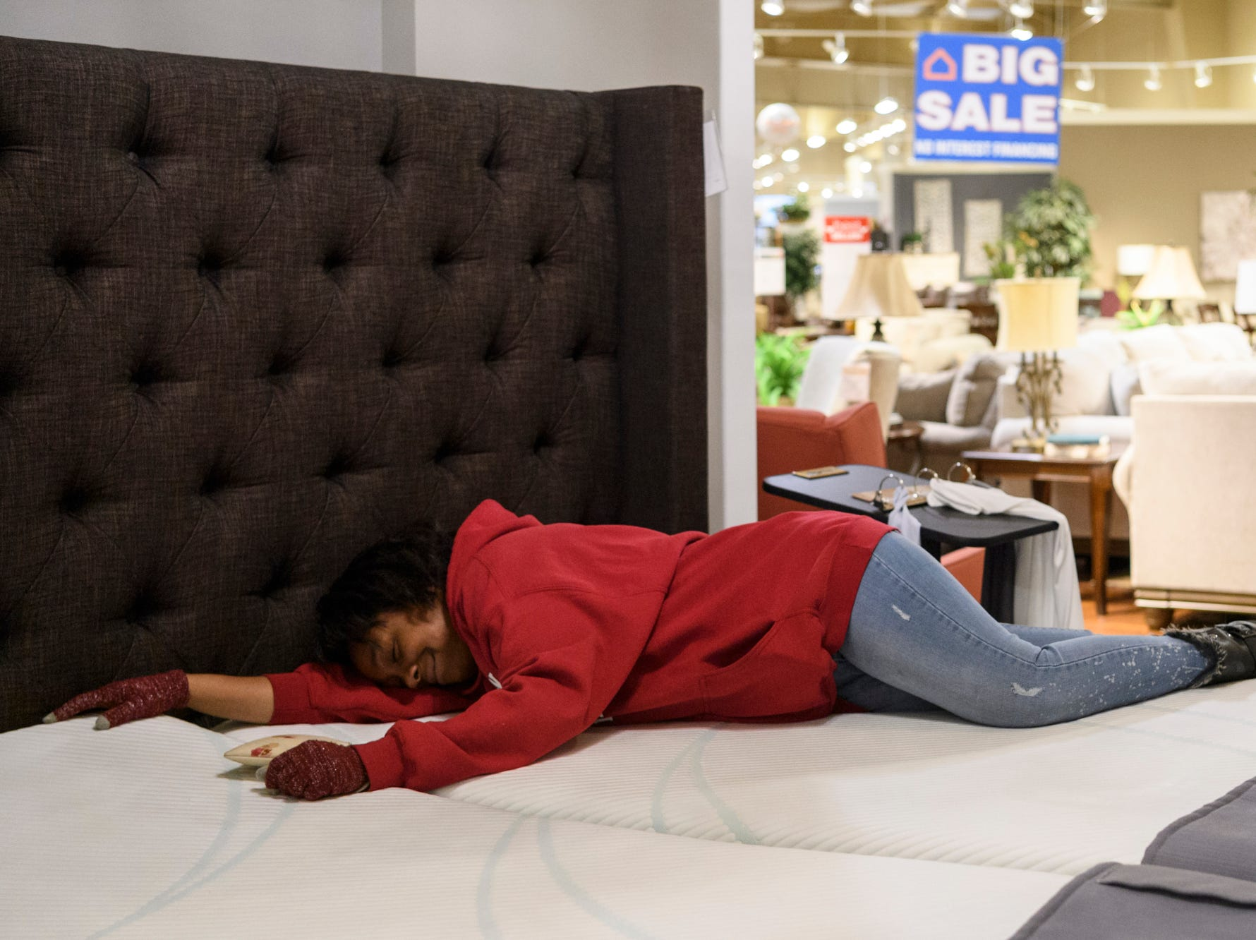 Photo taken for the 500th Habitat homeowner story that ran on April 21: Tamisha Dilworth tests out the comfort of a mattress as she shops for furniture at Ashley HomeStore in Evansville, Friday afternoon, March 1, 2019. While working for her Habitat house and sleeping on the couch or the floor at her father's house, she frequently dreamt about how good it would feel to have her own bed again.