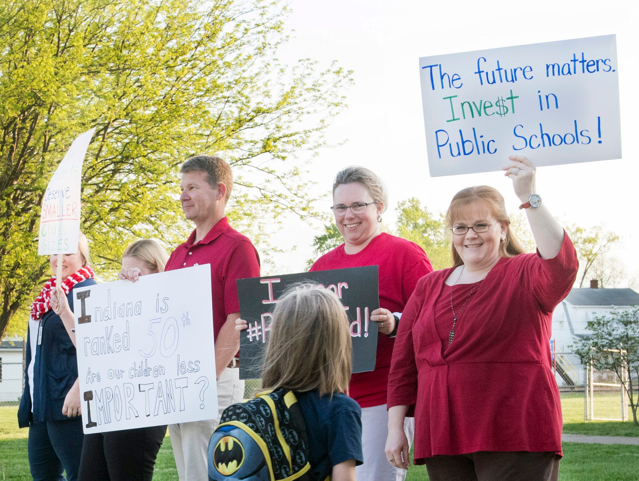 """Tekoppel Elementary teachers Bryan Norman, left, Michelle Adams-Smith, center, and Virginia Marcee, right, hold up signs as a student walks past while participating in Indiana's """"Red for Ed' Teacher Walk-in Tuesday, April 23, 2019. Teachers across Indiana participated in the walk-in to send a message to state legislatures."""