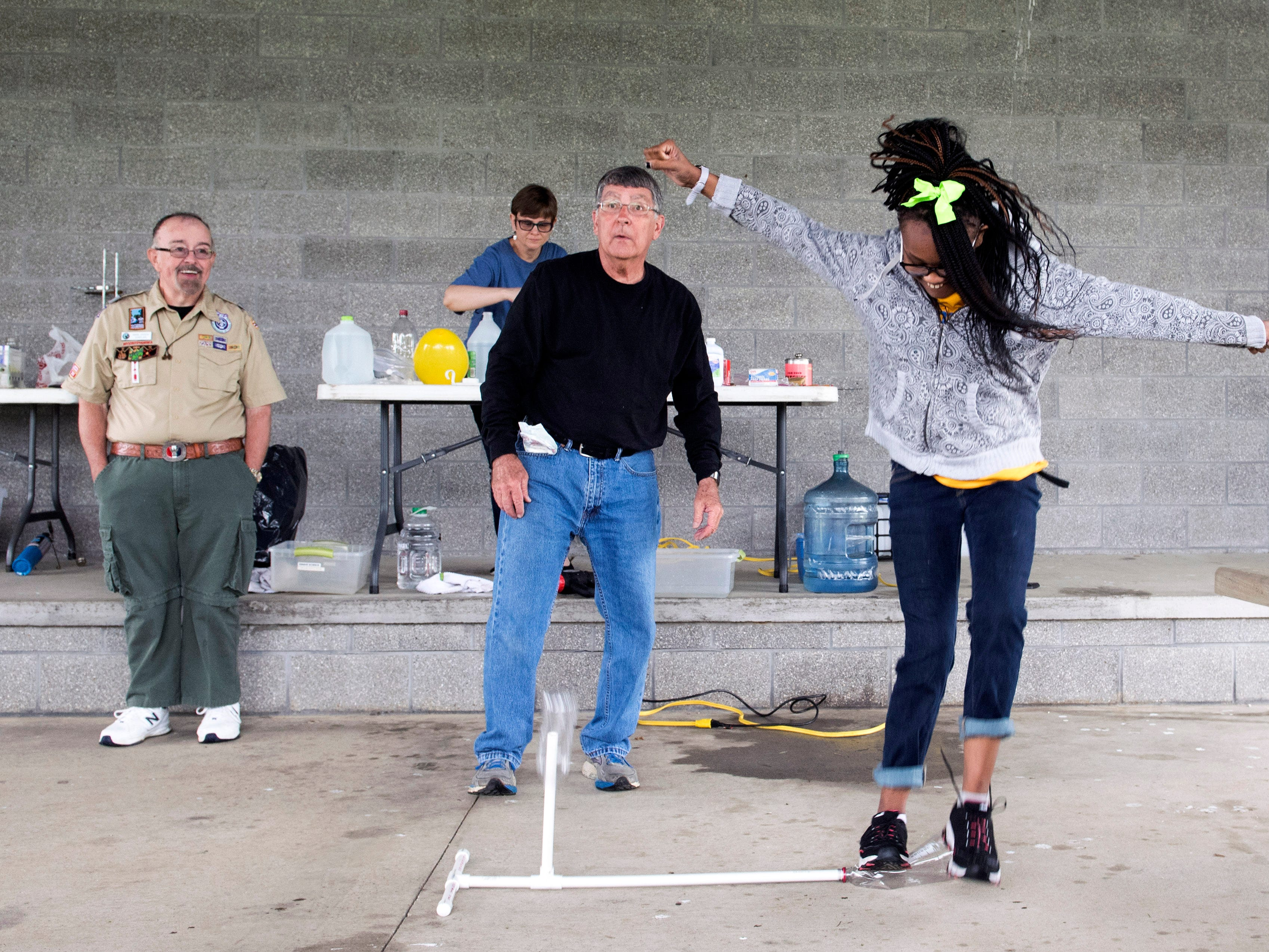 Thompkins Elementary seventh-grader Octaiva Mason, right, stomps on a POP! Rocket to launch a plastic battle in the air as Boy Scouts of America Chaplin Mark Dicken, left, and Evansville Museum's Jim Price teach science lessons during the Buffalo Trace Council's Exceptional Needs Field Day at the Eykamp Scout Center, Thursday, April 25, 2019.
