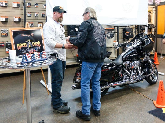 Robert Thiede of Fond du Lac receives a one year membership to Open Road HOG Chapter Saturday, May 4, 2019 at Open Road Harley-Davidson in Fond du Lac, Wis. from Mike Stoffregan of Fond du Lac. Thiede, a wounded Marine Corps. veteran,  was gifted a  2017 Harley-Davidson Road Glide Special from the Wisconsin-based Hogs For Heroes group. Doug Raflik/USA TODAY NETWORK-Wisconsin