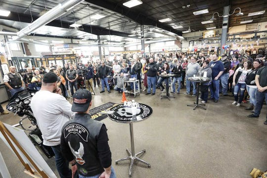 Motorcycle enthusiasts, including many militarily veterans, gather at Open Road Harley-Davidson in Fond du Lac Saturday as Marine Corps veteran Rob Thiede (front left) of Fond du Lac is gifted a 2017 Harley-Davidson Road Glide Special from the Wisconsin-based Hogs for Heroes group, represented by its president Kevin Thompson (front right).