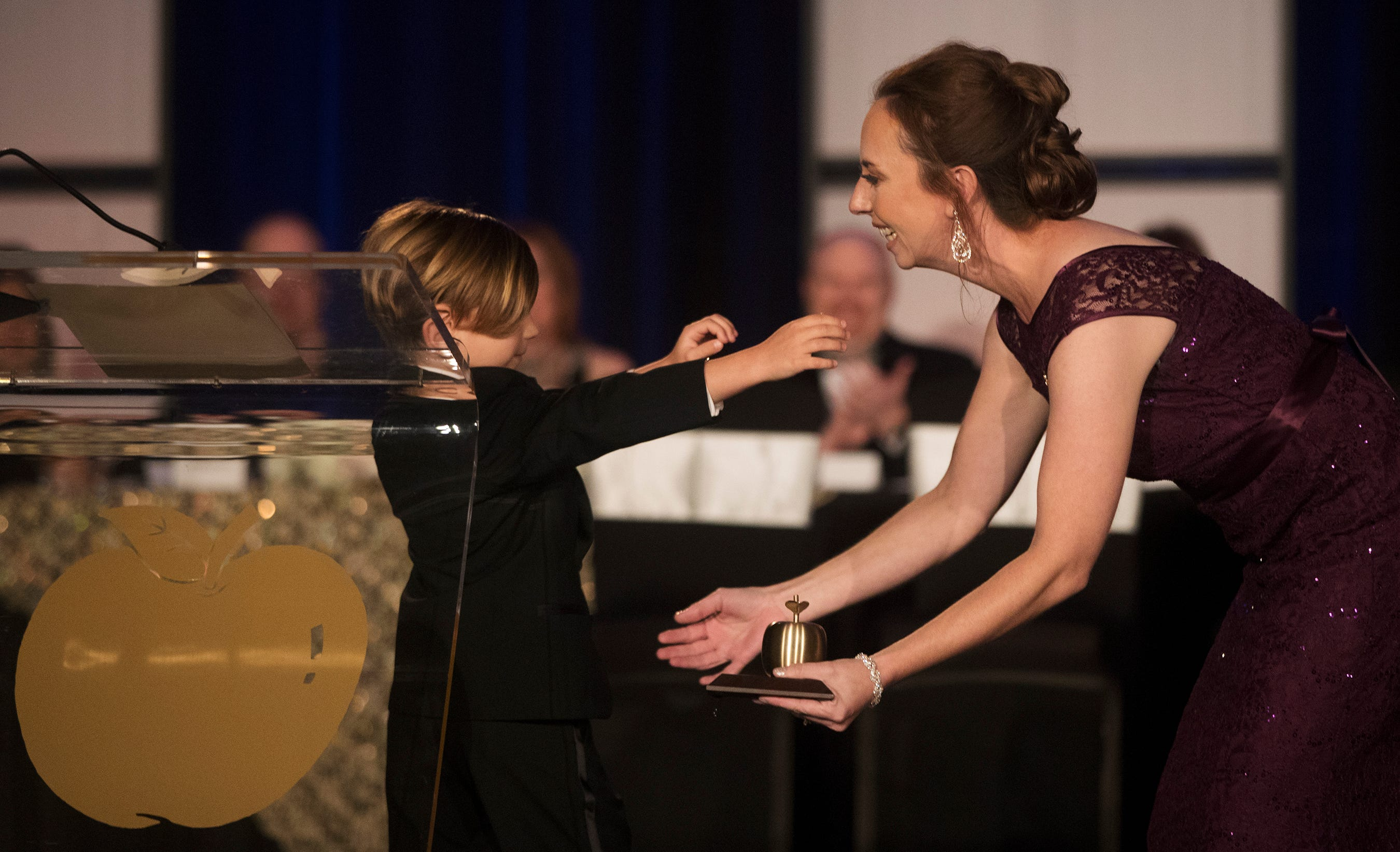 Heights Elementary School student Cason McNeff presents a Golden Apple to his teacher Kristina Caudill on Friday at the Golden Apple Teacher Recognition Banquet at the Hyatt Regency Coconut Point in Bonita Springs.