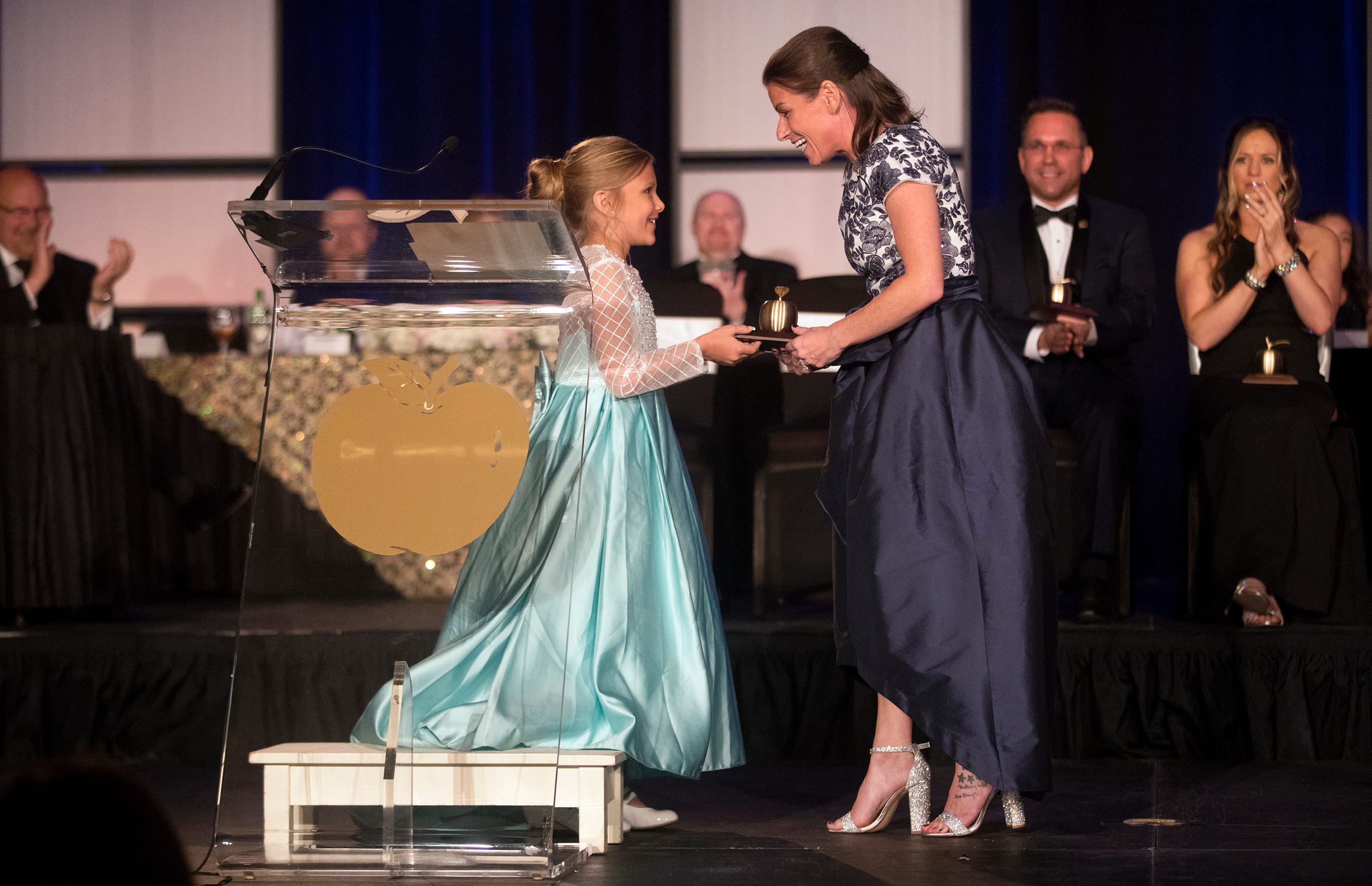 Gulf Elementary School student Makenzie Brown presents a Golden Apple to her teacher Kristina Gale on Friday at the Golden Apple Teacher Recognition Banquet at the Hyatt Regency Coconut Point in Bonita Springs.
