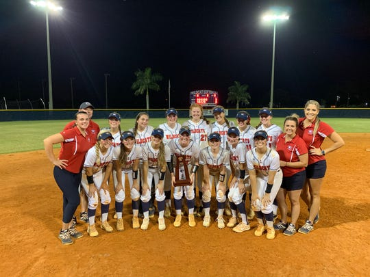 The Estero girls softball team celebrates with the district trophy following an 8-0 victory over Naples.