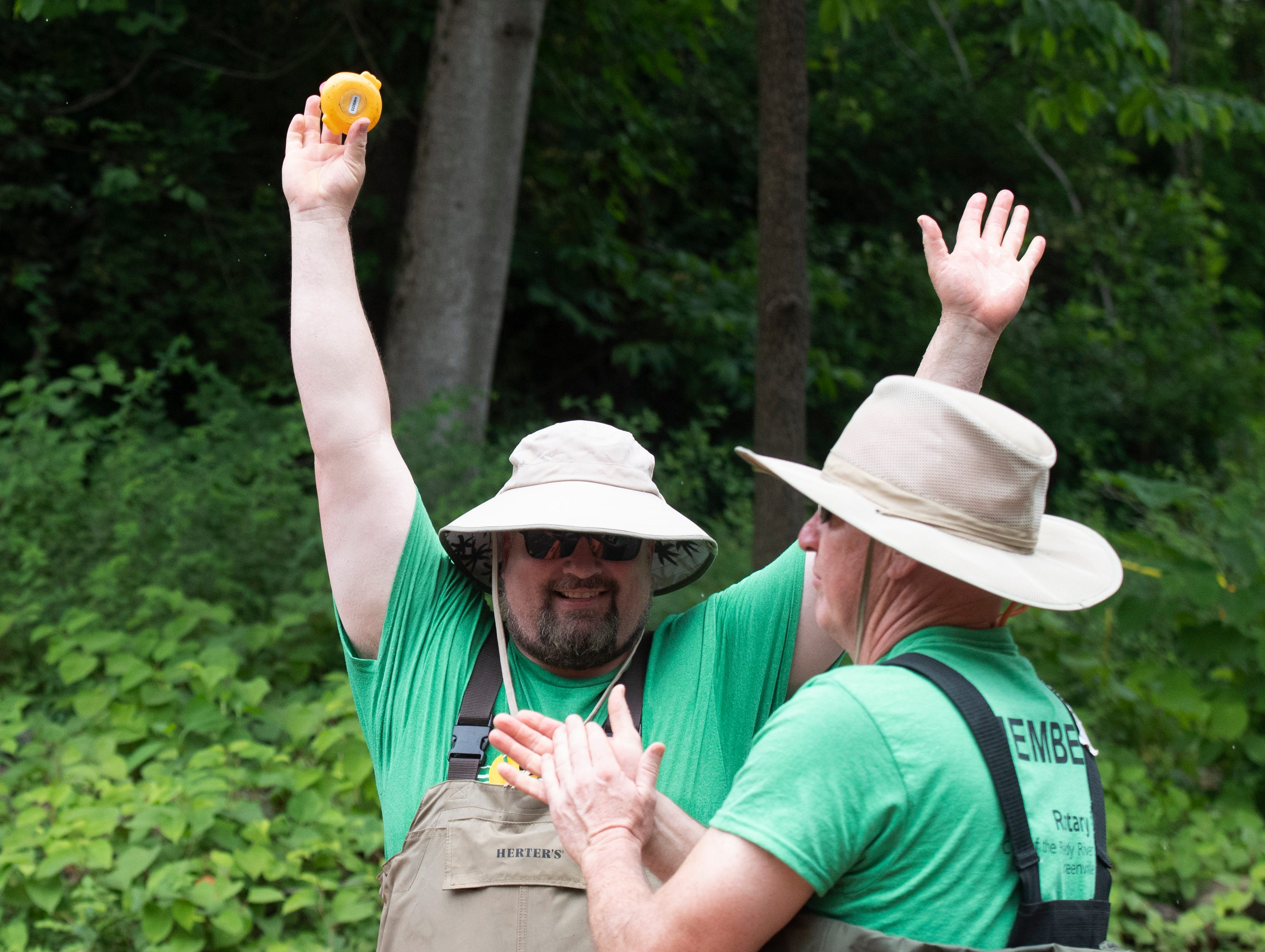Brothers Alan (left) and Ed Calloway celebrate the first rubber duck in the 2019 Reedy River Duck Derby in Falls Park on the Reedy Saturday, May 4, 2019.