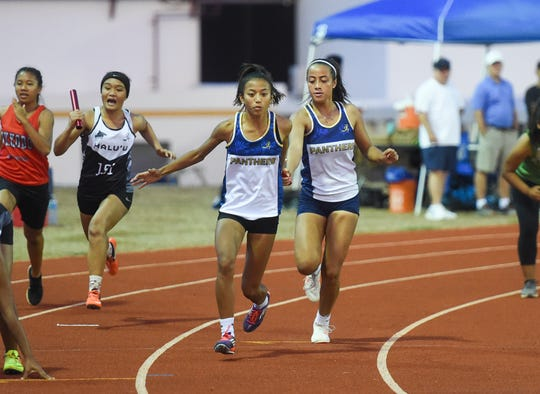 Guam High's Alexia Brown, right, hands the baton to teammate Mikayla Angoco in the Women's 4x100 Relay Varsity during the season's fifth IIAAG Track and Field meet at the John F. Kennedy High School Ramsey Field in Tamuning, May 3, 2019.
