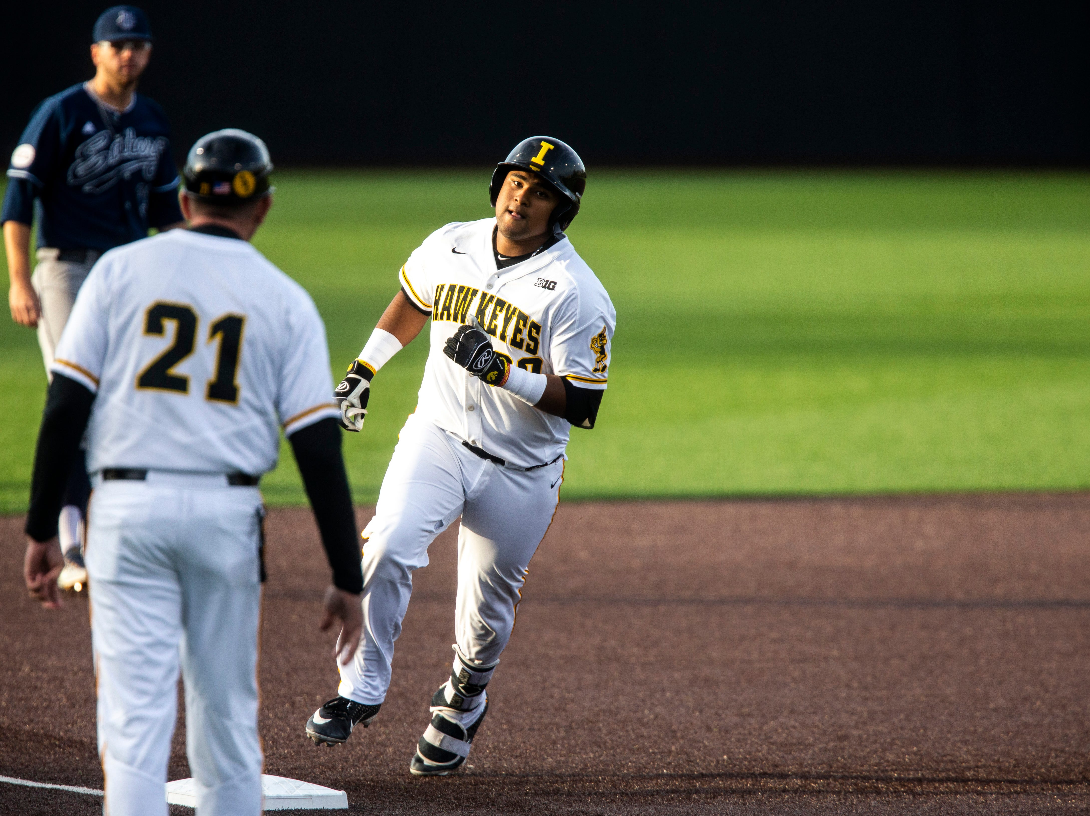 Iowa infielder Izaya Fullard (20) rounds third base past Iowa head coach Rick Heller during NCAA non conference baseball game, Friday, May 3, 2019, at Duane Banks Field in Iowa City, Iowa.