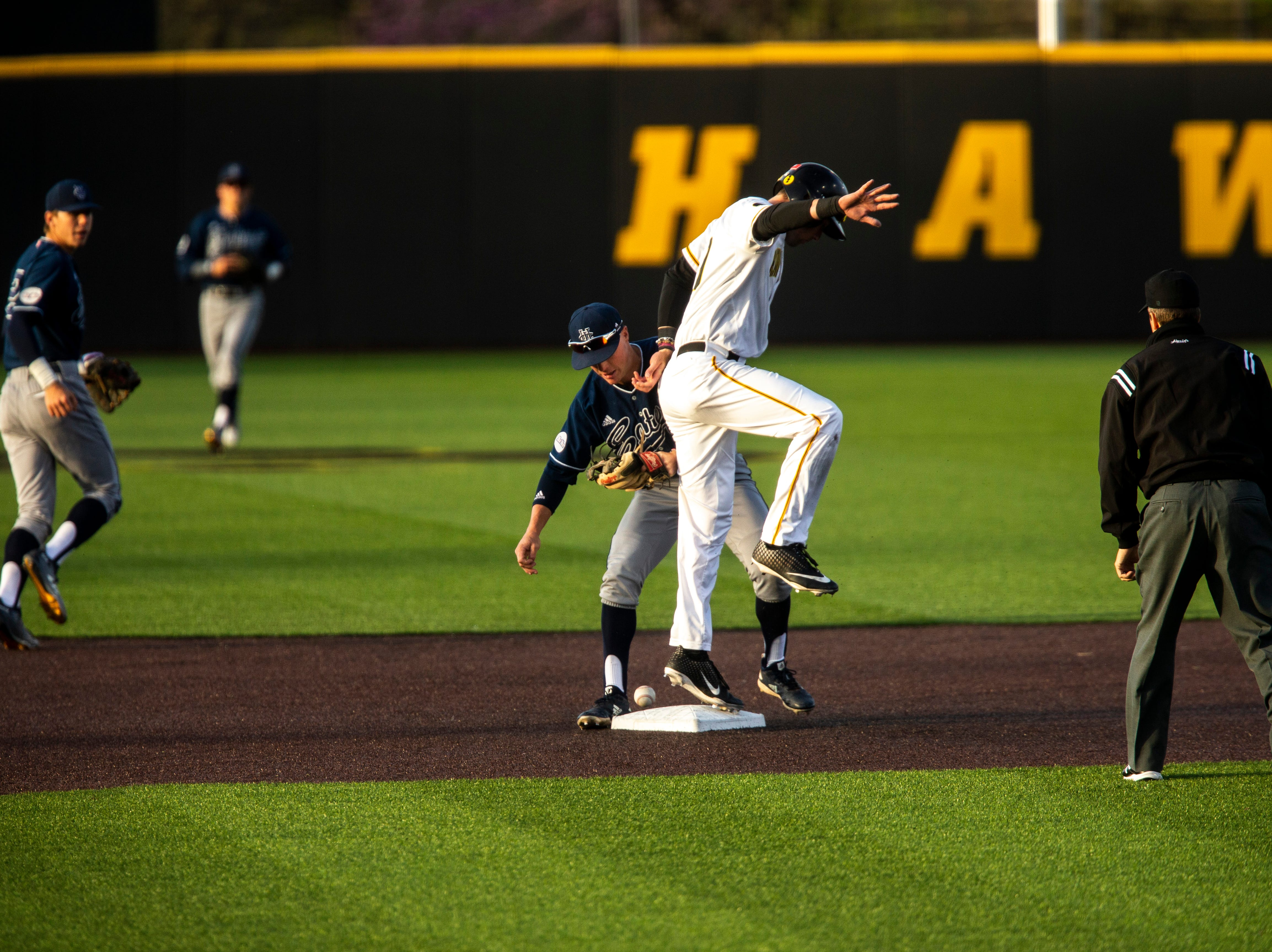 Iowa outfielder Ben Norman, right, attempts to keep his balance on second after sliding in safe following a dropped catch from University of California Irvine's Sam Ireland (5) during NCAA non conference baseball game, Friday, May 3, 2019, at Duane Banks Field in Iowa City, Iowa.