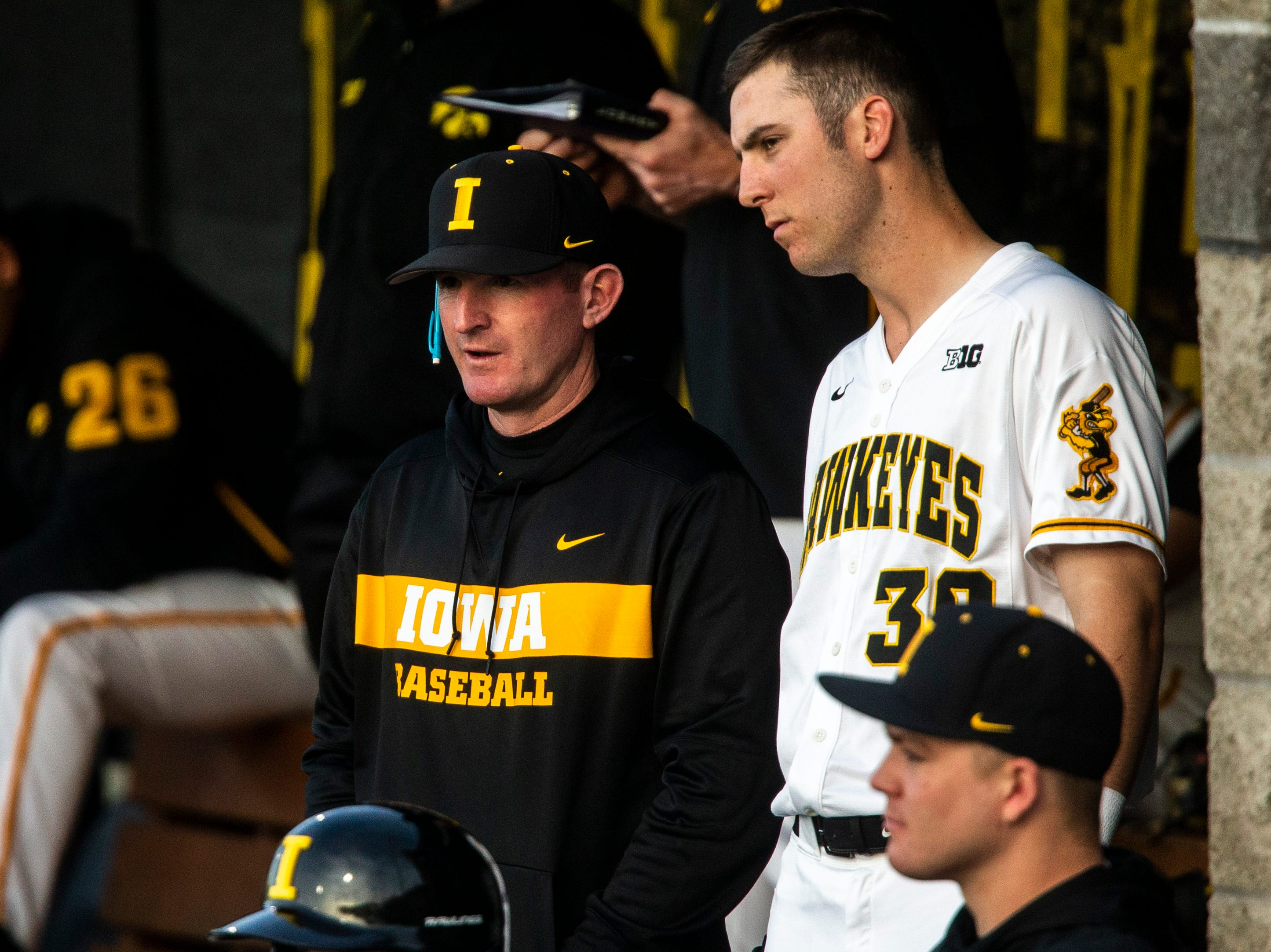 Iowa's Connor McCaffery (30) talks with Marty Sutherland, left, in the dugout during NCAA non conference baseball game, Friday, May 3, 2019, at Duane Banks Field in Iowa City, Iowa.
