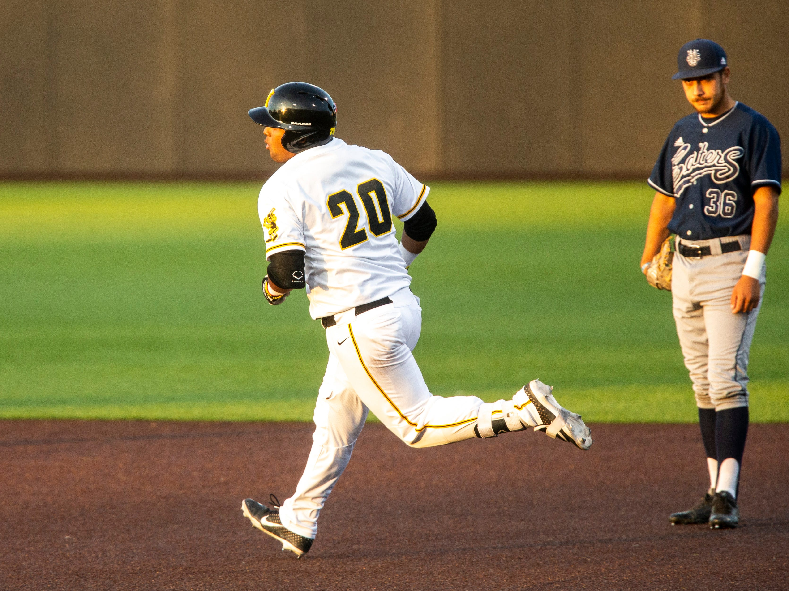 Iowa infielder Izaya Fullard (20) celebrates while rounding first past University of California Irvine's Adrian Damla (36) after hitting a home run during NCAA non conference baseball game, Friday, May 3, 2019, at Duane Banks Field in Iowa City, Iowa.