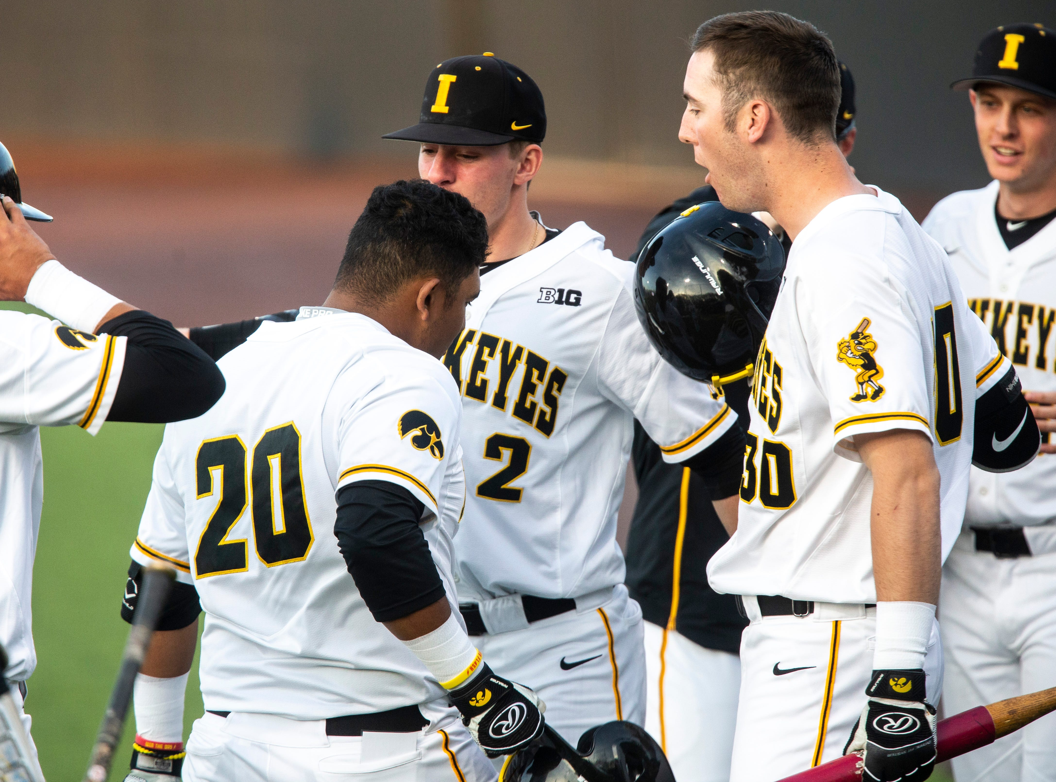 Iowa infielder Izaya Fullard (20) gets embraced by teammates Brendan Sher (2) and Connor McCaffery (30) after scoring a home run during NCAA non conference baseball game, Friday, May 3, 2019, at Duane Banks Field in Iowa City, Iowa.