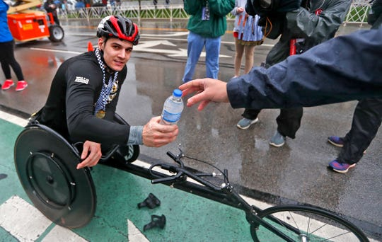 Brett Granatt gets a water and medals after crossing the finish line as the top men's wheelchair racer during the OneAmerica 500 Festival Mini-Marathon, Saturday, May 4, 2019.