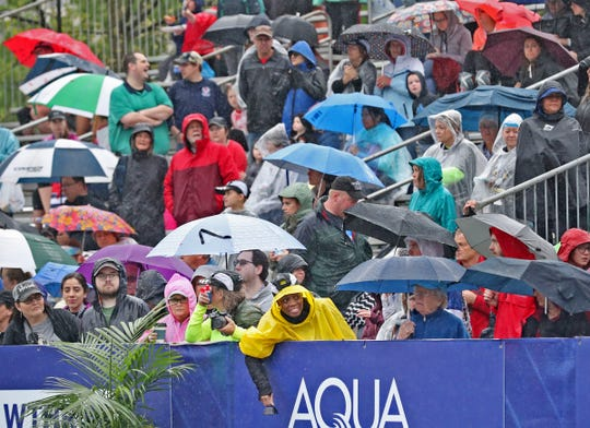 People wait under umbrellas at the finish line during the OneAmerica 500 Festival Mini-Marathon, Saturday, May 4, 2019.