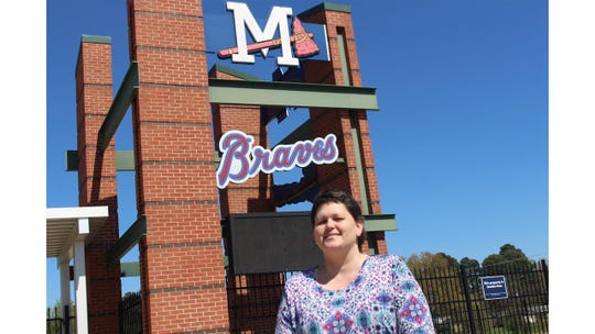 Christy Shaw poses in front of the Mississippi Braves sign at Trustmark Park in Pearl.
