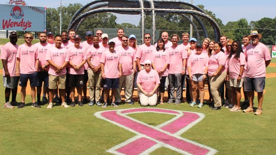 Members of the Mississippi Braves staff honored Christ Shaw, center, and her fight against breast cancer.