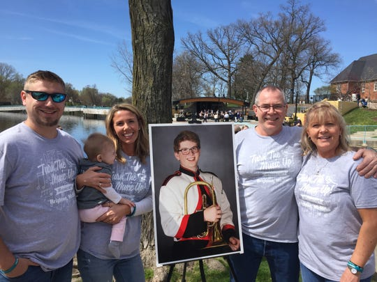 Andrew Leach, Alexis Nagy holding Addison Leach, Carl Nagy and Connie Nagy pose with a photograph of their late family member Carl. The Brighton High School Jazz Band played a tribute concert to their former band mate Saturday, May 4, 2019, at the grand reopening of Brighton's Mill Pond amphitheater.