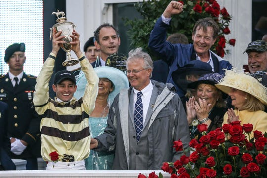 Kentucky Derby 2019 winner Country House's jockey Flavien Prat holds up the trophy as he stands next to trainer William Mott after Maximum Security was disqualified Saturday. May 4, 2019