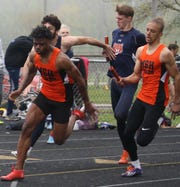 Triple winner and record-setter Angelo Grose prepares to take the baton for his anchor leg from cousin Alamar Grose as Mansfield Senior finishes first in the 4x100 relay at Friday's Galion Invitational.